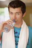 A young man drinking a bottle of water — Stockfoto