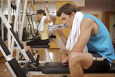 Portrait of young man taking a rest in gym — Stock Photo