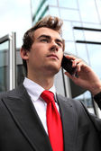 Young caucasian businessman at office exterior talking on cellphone — Stock Photo