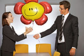 Businessman giving balloon to businesswoman in office — Stock Photo