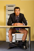 Portrait of businessman sitting without pants at office — Stock Photo