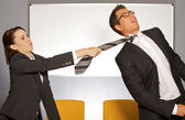 Businesswoman pulling businessman by tie — Stock Photo