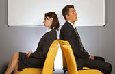 Businessman and woman sitting on chair back to back — Stock Photo