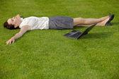Podnikatelka, ležící v parku s notebookem — Stock fotografie