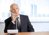 Businessman talking on telephone at office — Stock Photo