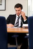 Empresário conversando no telefone fixo enquanto escrevia no papel — Foto Stock