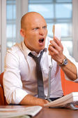 Businessman shouting on landline phone — Foto Stock
