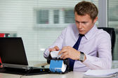 Businessman searching for card by laptop in office — Stock Photo