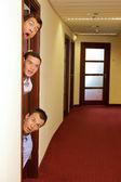 Affärsmän som kikar ut dörren — Stockfoto