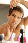 Young man combing his hair — Stock Photo
