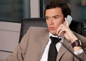 Businessman using telephone in an office — Stock Photo
