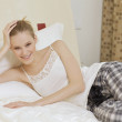 Woman Relaxing on bed - Stockfoto