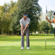Young man with his friend playing golf in golf course — Stock Photo