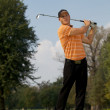 Young man swinging golf club — Stock Photo #3830073