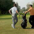 Young men standing in golf course by golf bag full of sticks — Stock Photo