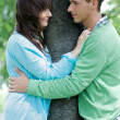 Young couple with arm around by tree — Stock Photo #3830269