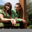 Portrait of young couple standing by wooden railing and smiling — Foto Stock