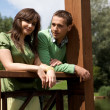 Portrait of young couple standing by wooden railing and smiling — Stock Photo