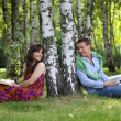 Stock Photo: Young couple holding books in park by tree trunk, looking at each other