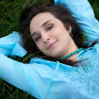 Stock Photo: Portrait of young woman lying on grass