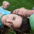 Stock Photo: Portrait of young woman lying on grass with boyfriend