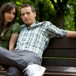 Young couple sitting on bench — Stock Photo