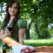 Portrait of young woman holding wineglass, sitting in park - Stock Photo