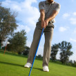 Man about to strike golf ball, low angle view — Stock Photo