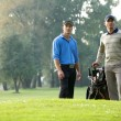 Young men standing with trolley in golf course - Stock Photo