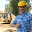 Portrait of architect showing thumbs up sign at construction site — Stock Photo