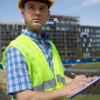 Architect using clipboard at construction site — Stock Photo