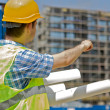 Engineer holding blueprint, standing in construction site — Stock Photo