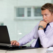 Businessman sitting with laptop at office — Stock Photo