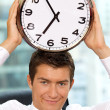 Portrait of smiling businessman holding clock to his head — Foto Stock
