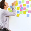 Businessman pointing at wall of sticky notes — Stock Photo