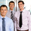 Royalty-Free Stock Photo: Three businessmen smiling at office, portrait