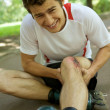 Skater injured and clutching leg — Stock Photo