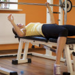 Stock Photo: Young womlift barbell on bench