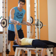 Stock Photo: Young mhelping young womlift barbell on bench