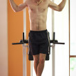 Man hanging on pull up bar - Stock Photo