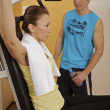 A young woman exercising with a personal trainer - ストック写真