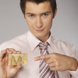 Royalty-Free Stock Photo: Young caucasian businessman holding gold credit card in hand