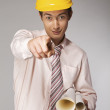 Young caucasian engineer with plans pointing finger at you — Stock Photo #3836144