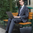 Young caucasian businessman using his laptop in park — Stock Photo