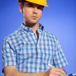 Architect in yellow hardhat writing on clipboard — Stock Photo