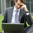 Stock Photo: Young caucasibusinessmsitting on grass reading bad news on laptop