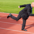 Businessman running on race track — Stock Photo