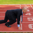 Businessman at the start line of running track — Stock Photo