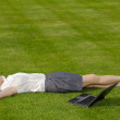 Businesswoman lying in park with laptop — Stock Photo