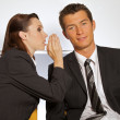 Businesswoman whispering in businessman's ear at office — Stock Photo